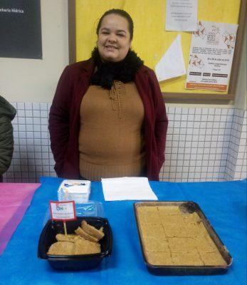 Foto da Tradutora Intérprete de Libras Juliana Sanches dos Santos, atrás da mesa com alguns pratos, sorrindo para a foto.