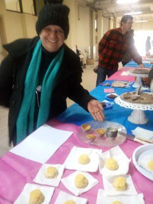 Foto da Tradutora Intérprete de Libras Elisabete Strelow de Castro, ao lado dos pratos, sorrindo para a foto.